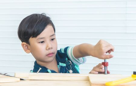 Little boy is working out tool on woodwork in workshop