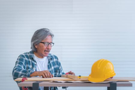 Old Construction Builder with tools and paper plan on working table