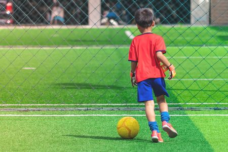 Child is dribbling Soccer ball on a field 스톡 콘텐츠