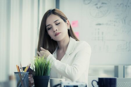 Tired office woman is using mobile phone to check her beauty and hair Stok Fotoğraf