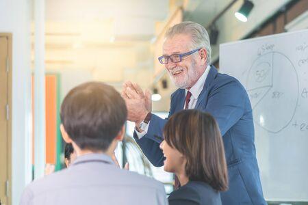 Le patron de la haute direction félicite l'équipe lors d'une réunion de bureau pour le succès de l'entreprise