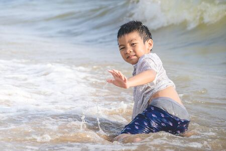 Little boy is playing with wave and sand on Pattaya beach Фото со стока - 126261120