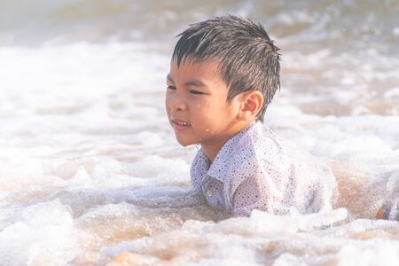 Little boy is playing with wave and sand on Pattaya beach