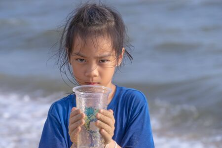 Children is holding Plastic cup that he found on the beach for enviromental clean up concept