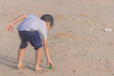 Little boy is cleaning up garbage on the beach for enviromental clean up concept