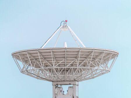 Large White Satellite Dish receiver on blue background 스톡 콘텐츠
