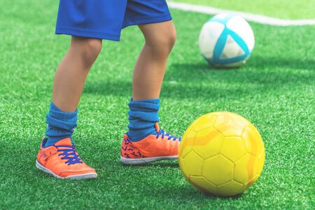 Child feet is dribbling Soccer ball on a field