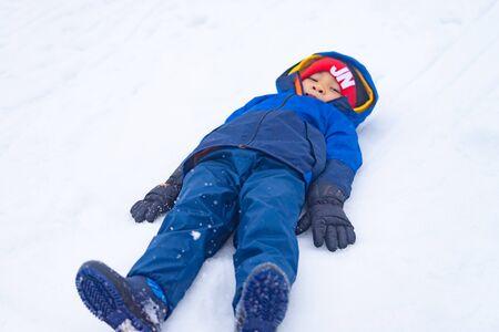 Little boy is lying down on snow