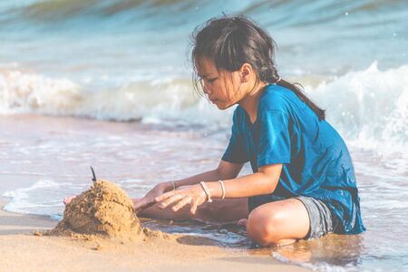 Little girl is playing with wave and sand on Pattaya beach