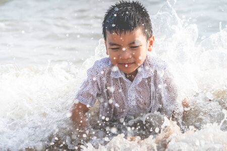 Little boy is playing with wave and sand on Pattaya beach Фото со стока - 128218975