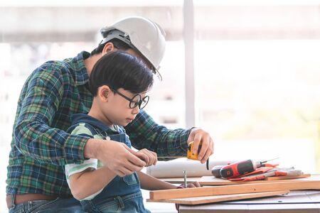 Little Boy uczy się pracować na drewnie i być budowniczym od swojego ojca rzemieślnika