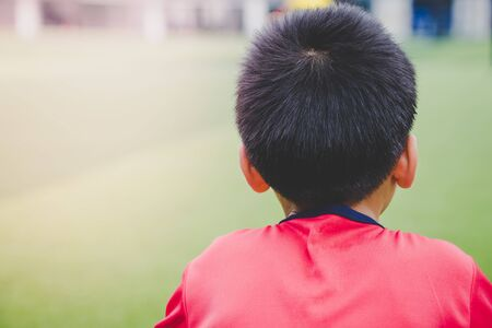 Little boy is relaxing in soccer training field Imagens