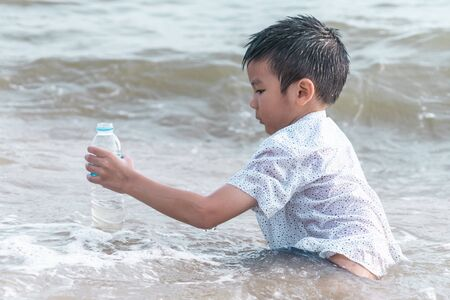 Children is holding Plastic bottle that he found on the beach for enviromental clean up concept