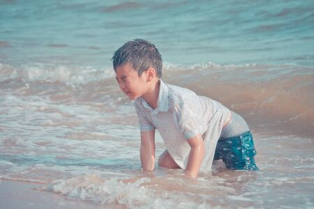 Little boy is playing with wave and sand on Pattaya beach Фото со стока - 129964143