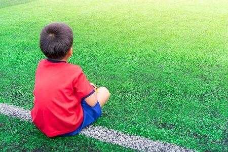 Little boy is relaxing in soccer training field Stockfoto