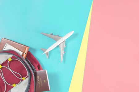 Air plane is flying out of a traveler backpack accessories on blue yellow pink