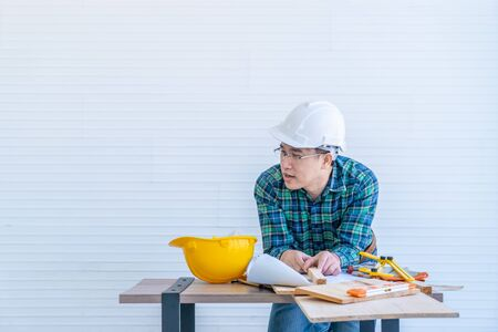 Construction wooden Builder with tools and paper plan on working table