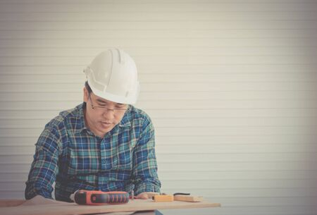Construction wooden Builder with tools and paper plan on working table vintage tone Stockfoto