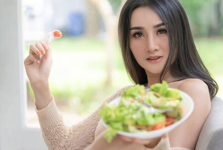 Woman is holding a big plate of salad eating at home