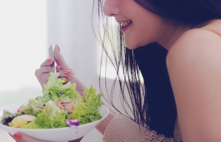 Healthy Sexy young woman is eating green salad for healthy lifestyle food concept