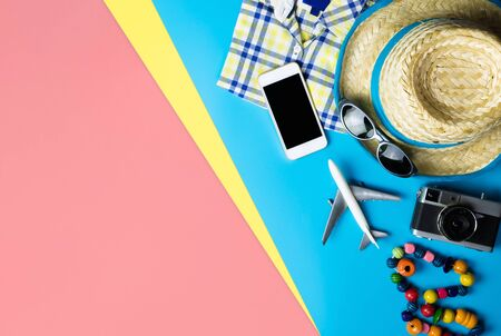 Summer travel fashion and accessories travel top view flatlay on blue yellow pink