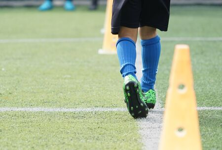 Child feet is practicing running and moving on soccer field