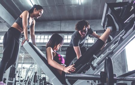 Woman is working out on a leg machine with male trainer beside to help her. Stok Fotoğraf