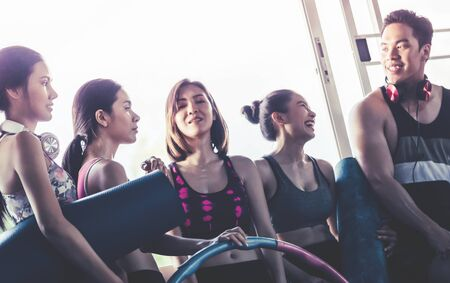Young Group of healthy friends is working out in Fitness Gym with workout equipment