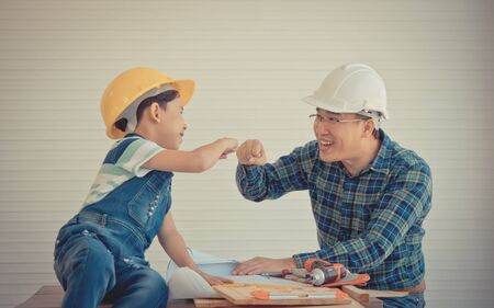 Father and Son fist bump for success Team work concept in construction industry in vintage tone. Family activity together for parent and child bonding concept.