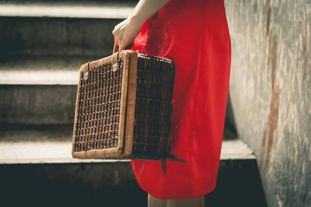 Vintage Chinese woman traveler in red holding a vintage travel luggage for Retro Vacation holidays chinese new year travel concept.