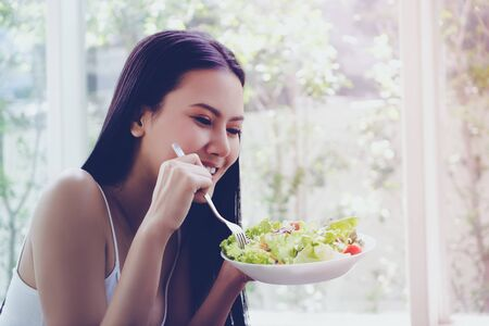 Woman is enjoying Vegetable salad as her monring breakfast at home for healthy eating and lifestyle beatiful concept. Slim woman eating salad for body weightloss control.
