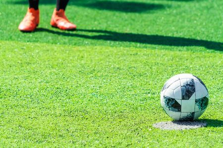 Feetballer foot standing near the penalty spot ready to kick pernalty on soccer pitch. Sport Determination and fearless concept.