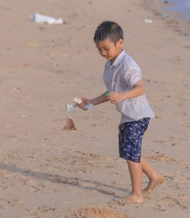 Little boy is cleaning up garbage and plastic waste on the beach for enviromental clean up and ecology conservation concept.