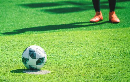 Kick foot in soccer boot standing on soccer field ready to kick the football, For youth Football Academy training concept Stock Photo