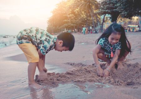 Two siblings Asian children is playing with wave and sand in Pattaya Beach Thailand for family and kid summer holidays concept Stok Fotoğraf