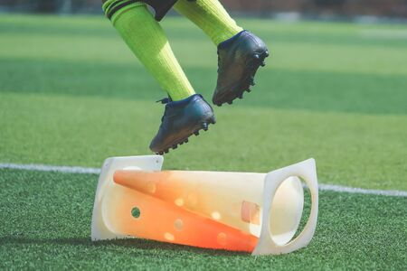 Child feet with football boot is practicing Jumping over the cone on soccer field, For children Soccer academy training concept.