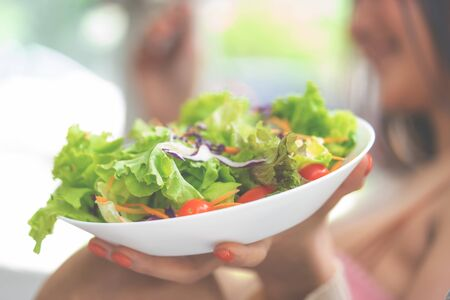 Healthy beauty young Asian woman is eating green salad for healthy lifestyle food concept with fork and tomatoes going in her mouth Stok Fotoğraf