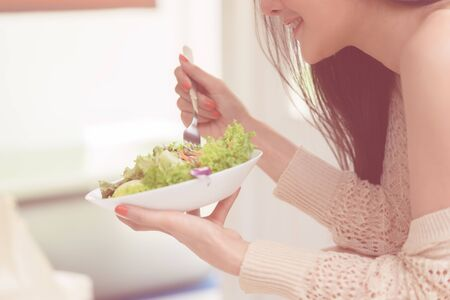 Healthy beauty young woman is eating green salad for healthy lifestyle food and eating concept