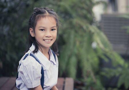 Portrait of Happy Thai student girl sitting in green garden