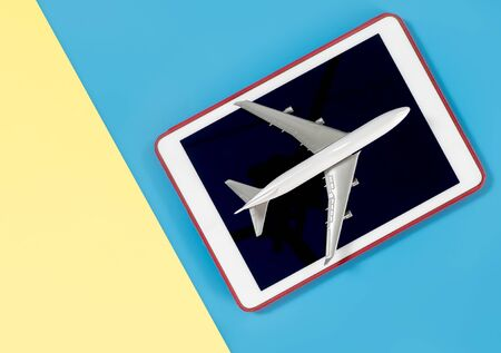tablet for copy space with plane for travel concept on blue yellow pink Stok Fotoğraf