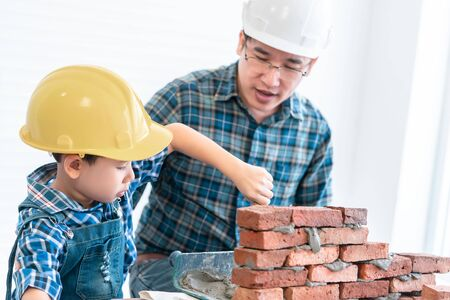 Little Boy is learning to work on Brickwall and be a builder from his craftman father in vintage tone, Family working together on house renovation for family bonding togetherness. Stock Photo