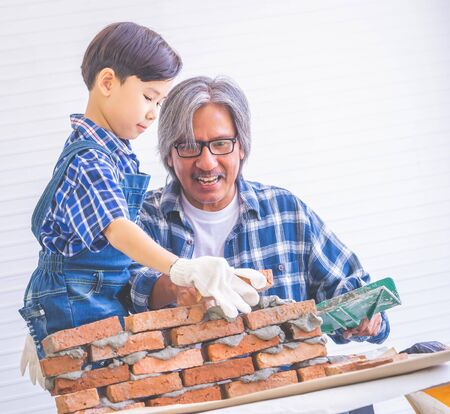 Little Boy is learning to work on Brickwall and be a builder from his craftman father in vintage tone, Family working together on house renovation for family bonding togetherness.