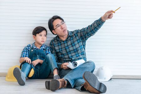 Construction Father is teaching his son about future career and dream, For parenting and family togetherness concept. Stock Photo