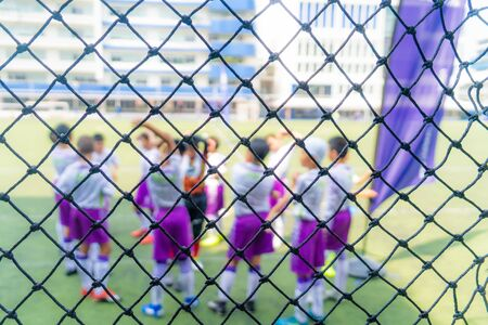 Children soccer team is warming on soccer field before a competition match, blurred behind the net for kid sport background and backdrop.