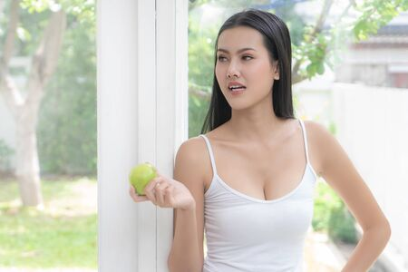 Healthy body beautiful asian woman is eating green apple at home for healthy eating and healthy lifestyle concept.