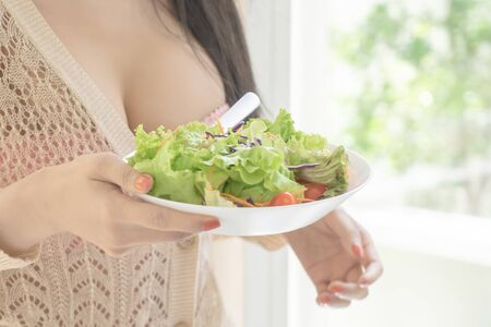 Healthy young woman is eating green salad for healthy lifestyle food and bodycare beauty concept Stok Fotoğraf