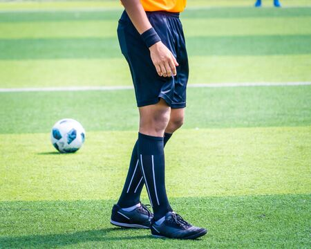 Soccer football referee leg and foot on a soccer competition field stadium with yellow shirt Stok Fotoğraf