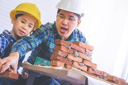 Der kleine Junge lernt, wie man von seinem Baumeister-Vater eine Ziegelmauer für das zukünftige Bildungskonzept des Familienberufs baut.