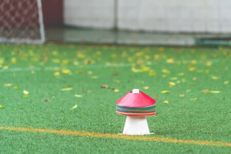 Colorful sport cone and marker for soccer and other sport training on a meadow grass field for soccer academy and sport training concept background. Фото со стока - 133466252