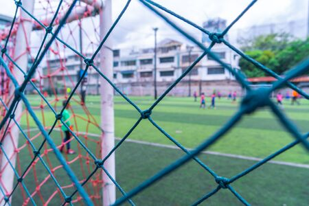 Kid is training soccer football in blur background behind the net